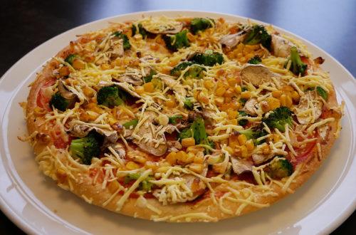 Vegane Pizza von Hallo Pizza! leicht seitlich auf weißem Teller
