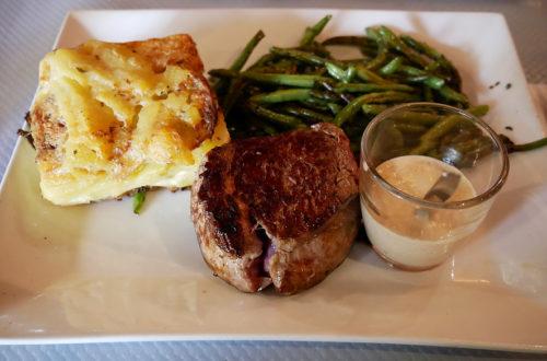 Rindersteak mit Sauce, Kartoffelgratin und Bohnen im L'Apollinaire Paris