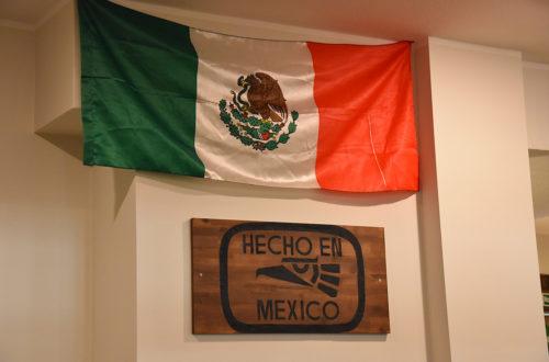 Mexikanische Flagge und Holzschild an der Wand hängend