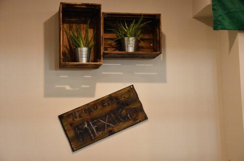 Braune Kästen mit Pflanzen an der Wand und Schild