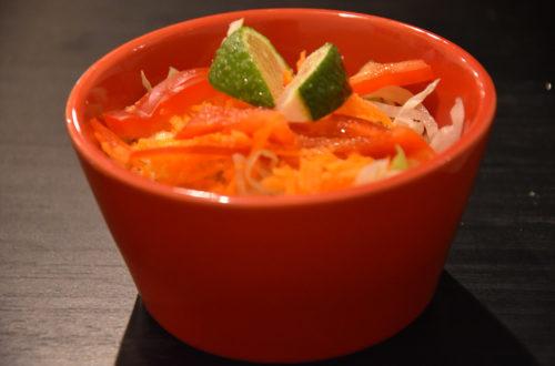 Krautsalat in roter Schüssel mit Limettenstückchen dekoriert