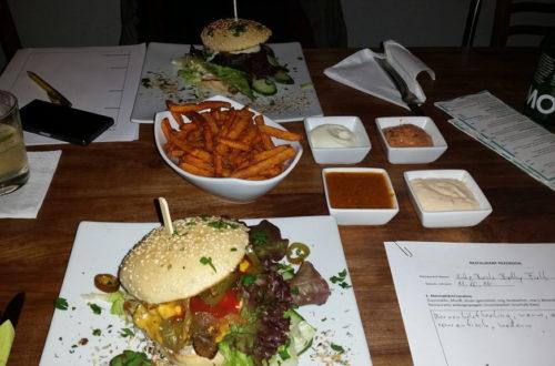 Komplettes Essen auf Tisch mit zwei bürgern, Süsskartoffelpommes und Dips