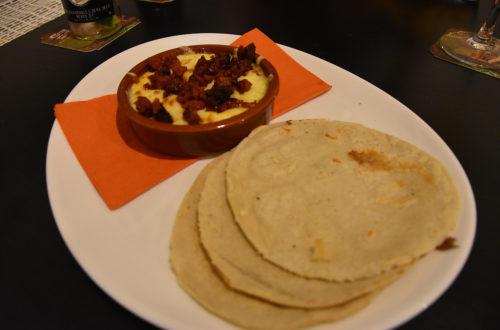 Fleischhaltige Vorspeise mit Fladen und Schüssel auf weißem Teller