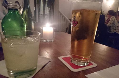 Lemonaid und Astra Bier in Gläsern auf Holztisch