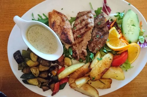 Fleisch Mix mit Sauce und Salatbeilage auf weißem Teller von oben