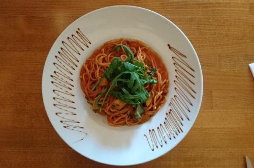 Veganes Spaghetti-Gericht mit Rucola auf weißem Teller von oben