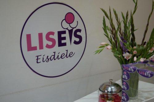LISEIS Logo an weißer Wand mit Blumen davor
